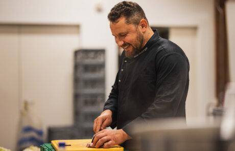 Koch lächelnd bei der Arbeit